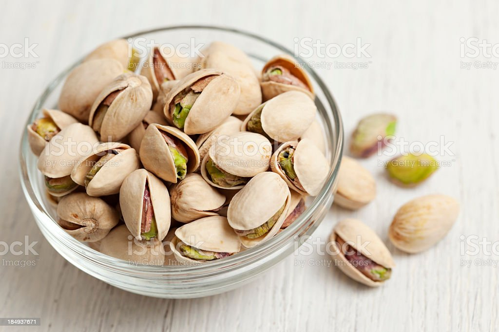 Pistachio nuts in a glass bowl stock photo