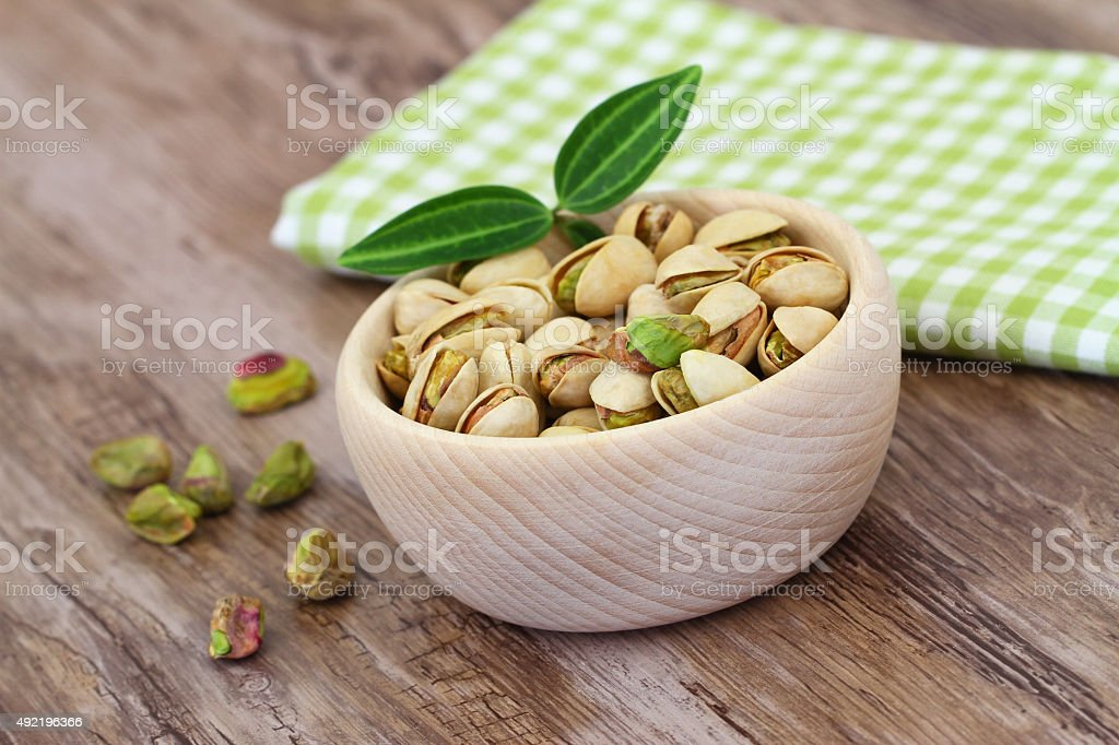 Pistachio nuts in wooden bowl on checkered cloth stock photo