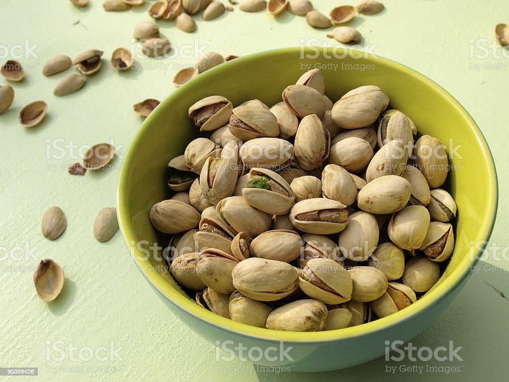 Pistachio nuts in yellow green bowl stock photo