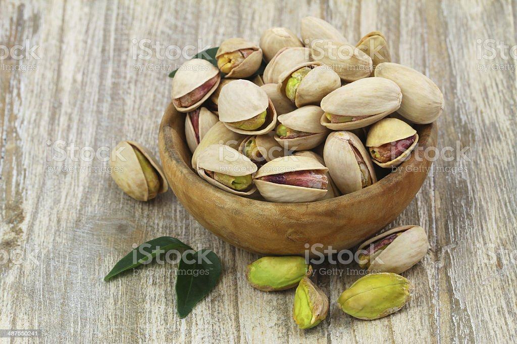 Pistachios in wooden bowl with copy space stock photo