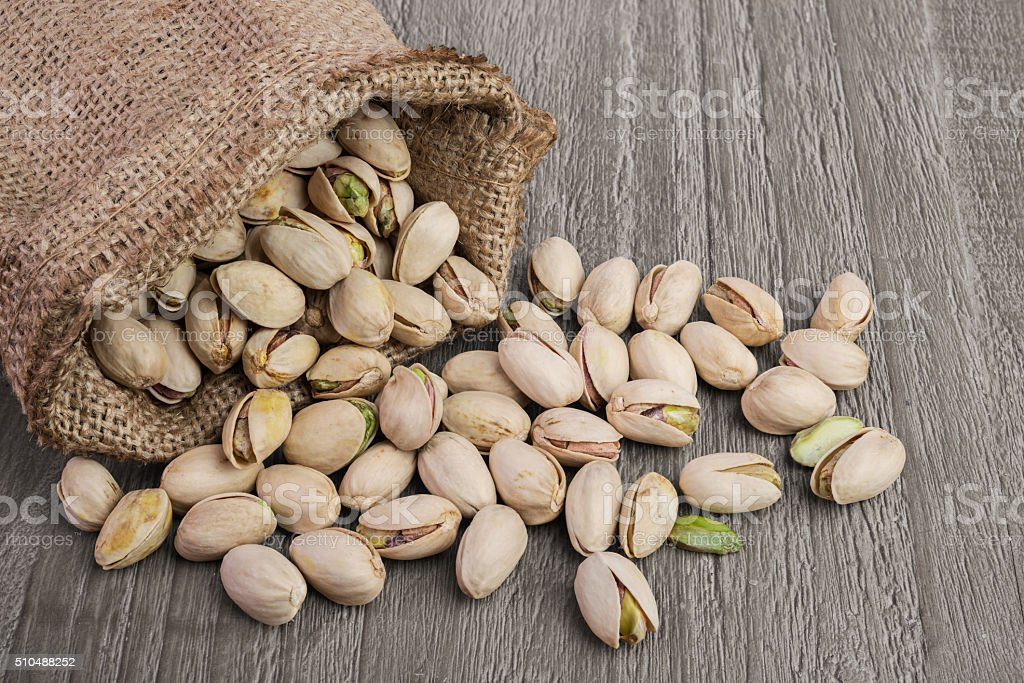 Pistachios on wooden table stock photo