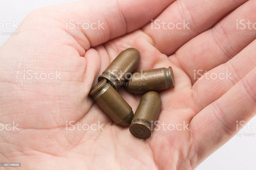 Pistol bullets in a hand stock photo
