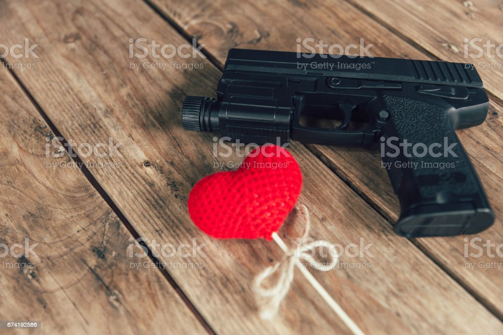 pistol gun and love red heart on wood background stock photo
