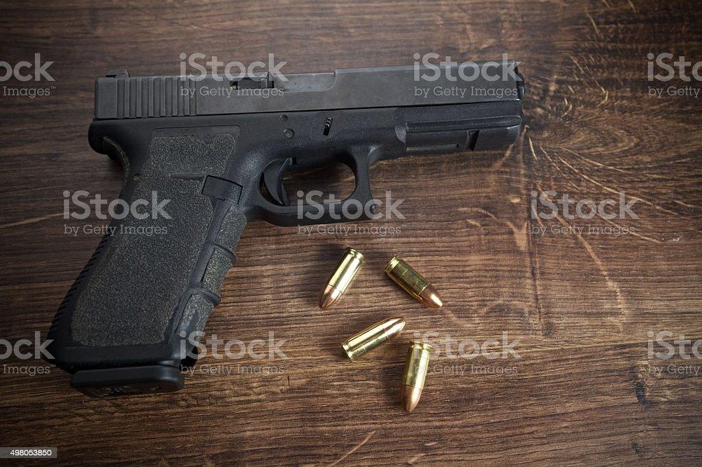 Pistol gun on wooden background stock photo
