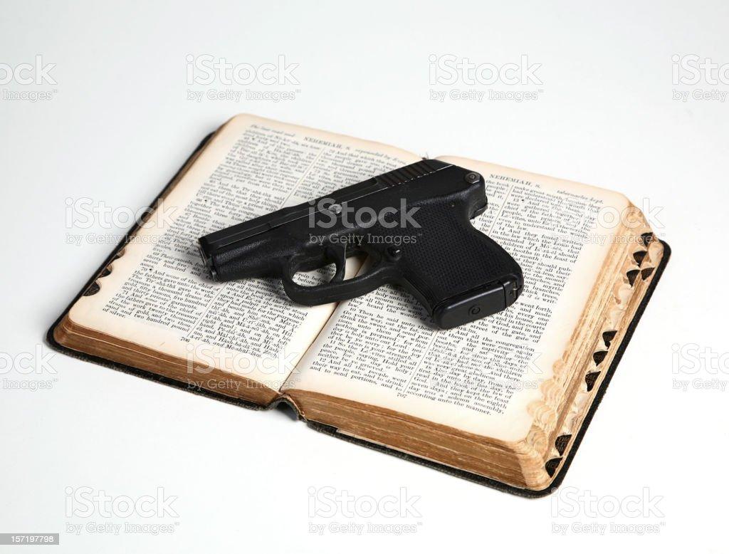 Pistol on Open Bible royalty-free stock photo