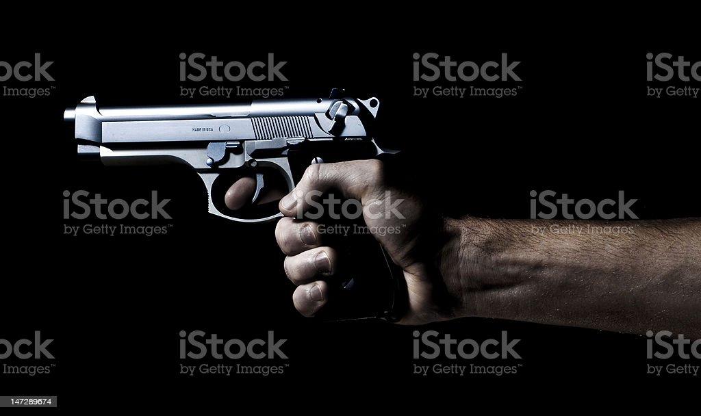 pistol or hand gun being shot in the dark stock photo