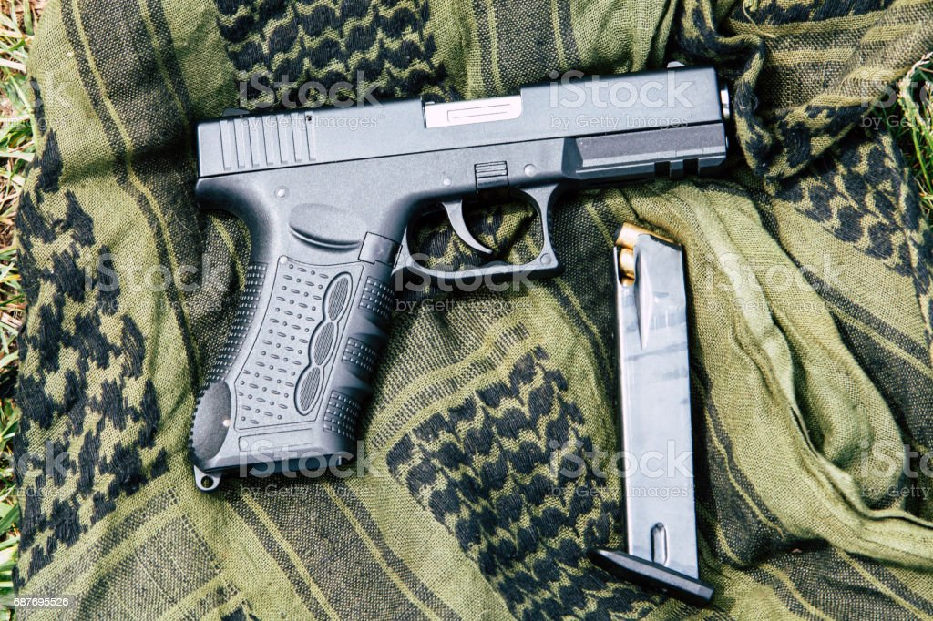 A pistol with a magazine on a green background stock photo
