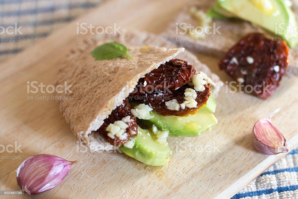 Pita bread with avocado and sundried tomatoes stock photo