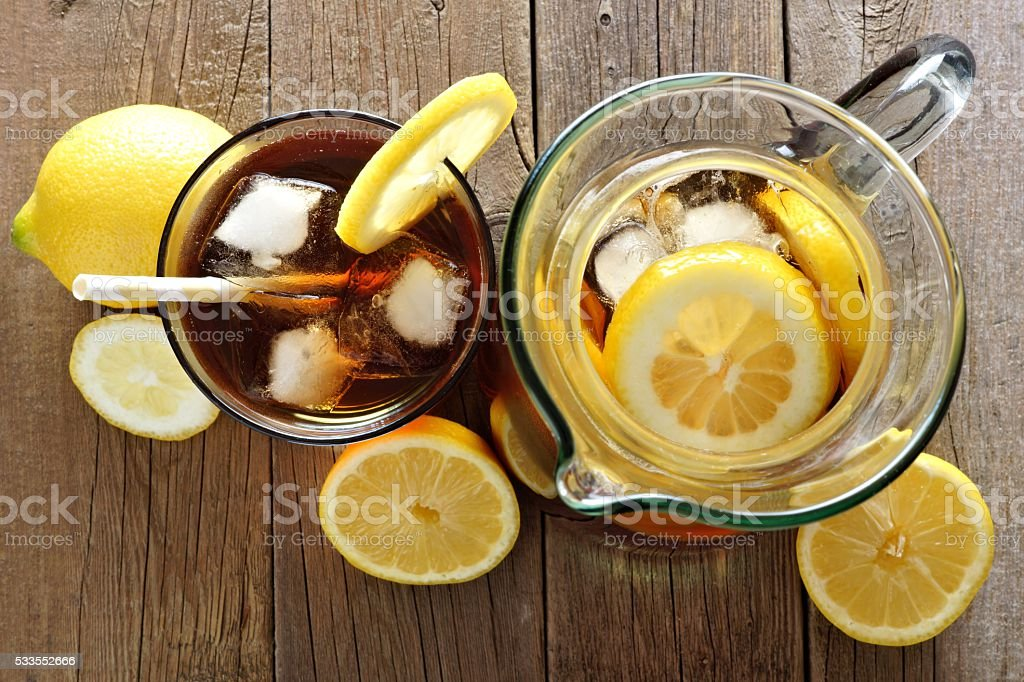 Pitcher and glass of iced tea, downward view on wood stock photo