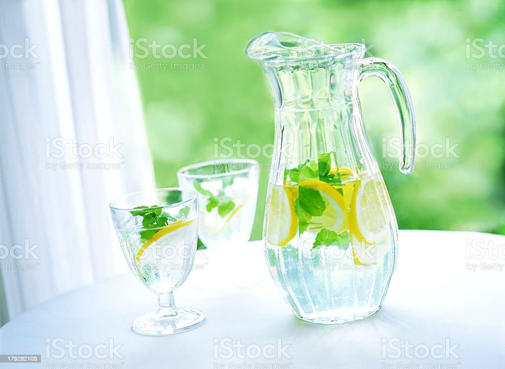 Pitcher and glasses of lemon water royalty-free stock photo