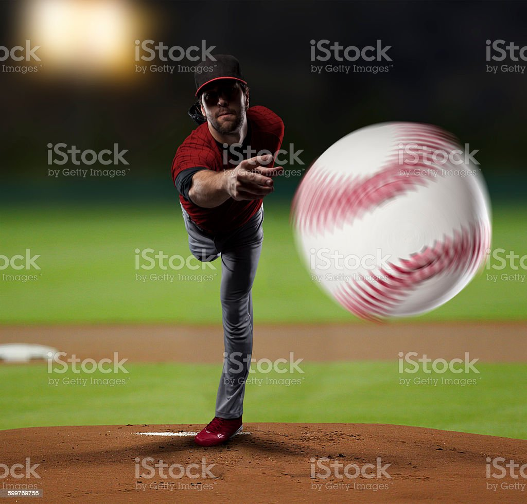 Pitcher Baseball Player with a red uniform on baseball Stadium.