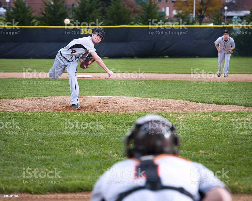 Pitcher following through pitching motion, ball in mid-air royalty-free stock photo