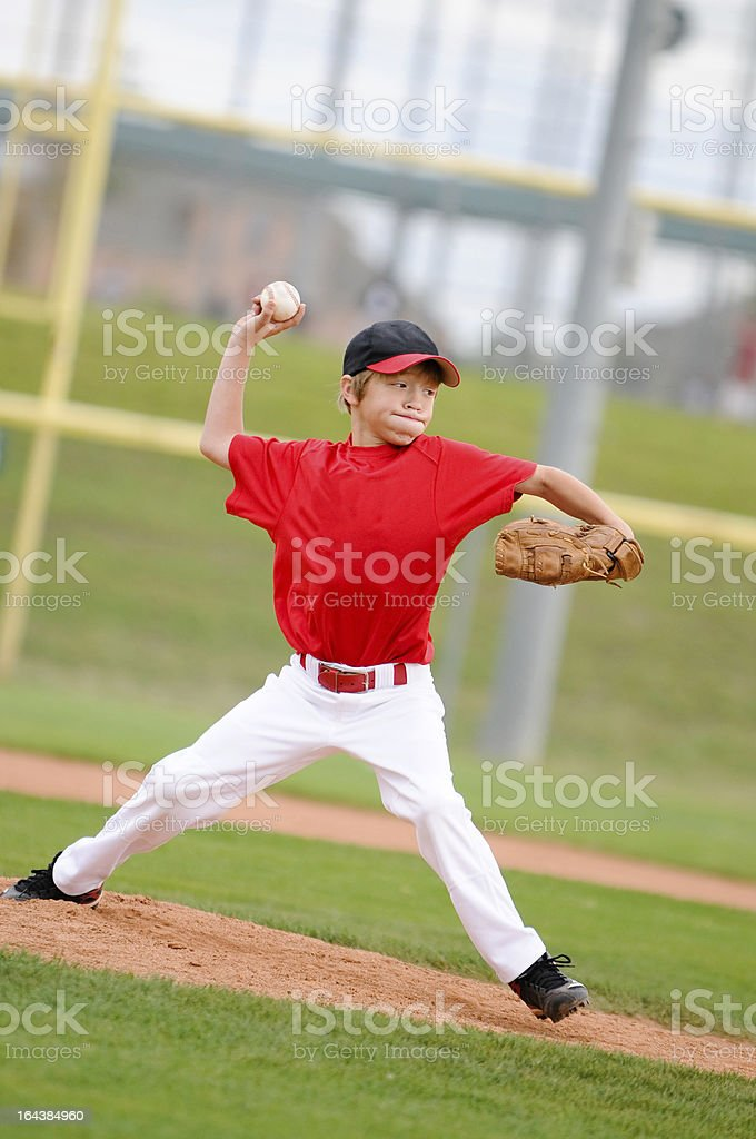 Pitcher in red throwing the pitch. stock photo