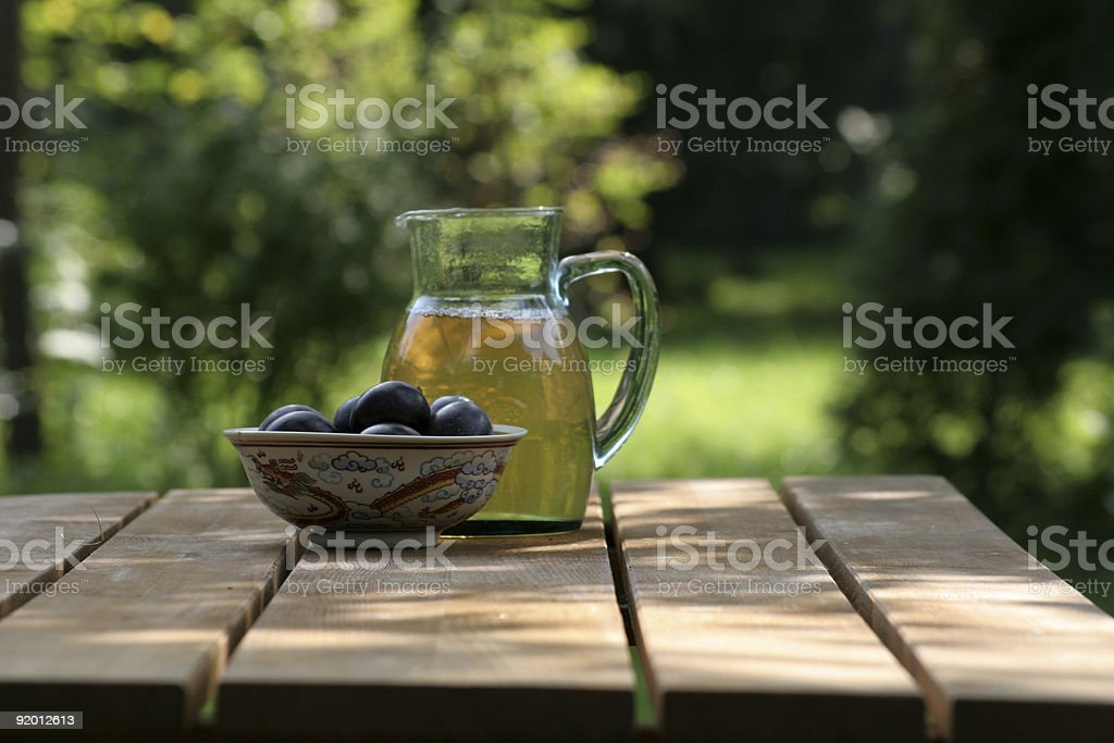 Pitcher of iced tea and plums on wooden table in the garden royalty-free stock photo