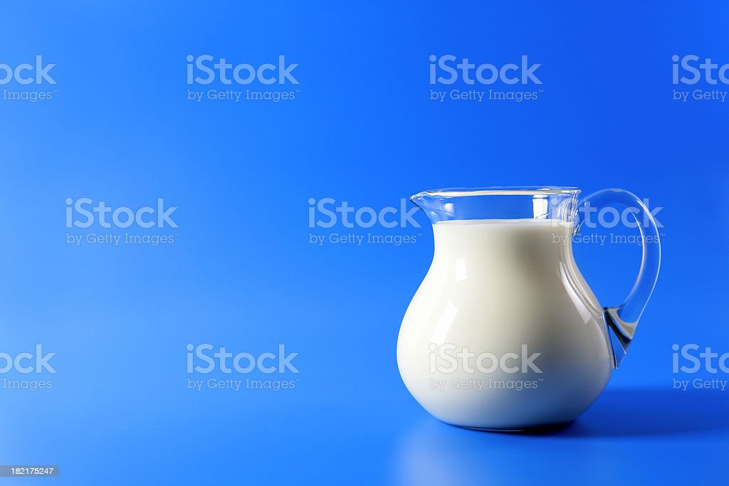 Pitcher of milk on blue royalty-free stock photo