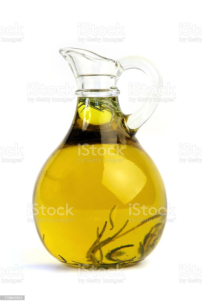 Pitcher of olive oil with rosemary royalty-free stock photo