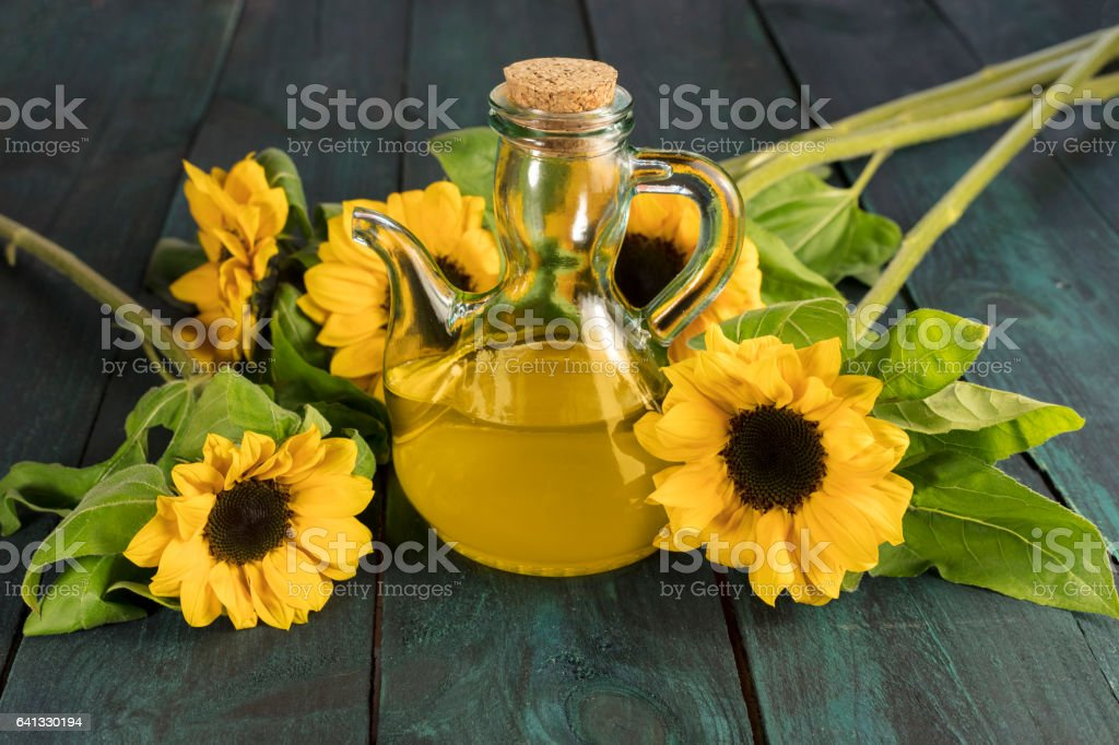 Pitcher of sunflower oil with flowers and copyspace stock photo