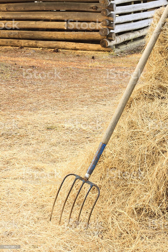 Pitchfork On Farm With Log Cabin stock photo