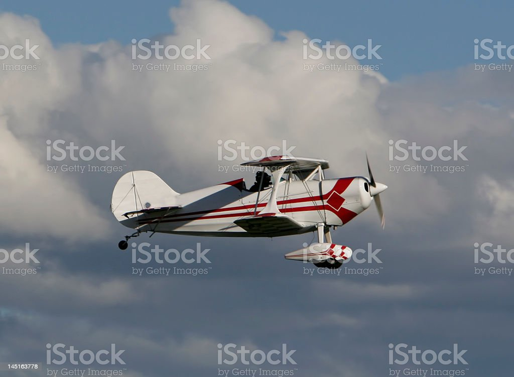 Pitts Special Flying in White Billowy Clouds stock photo
