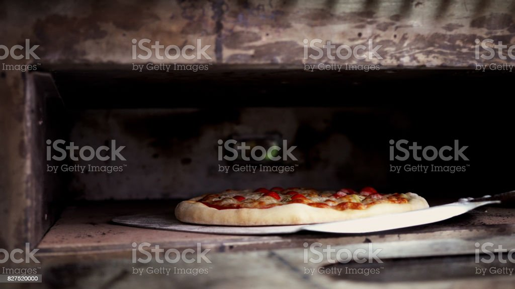 Pizza at the oven stock photo