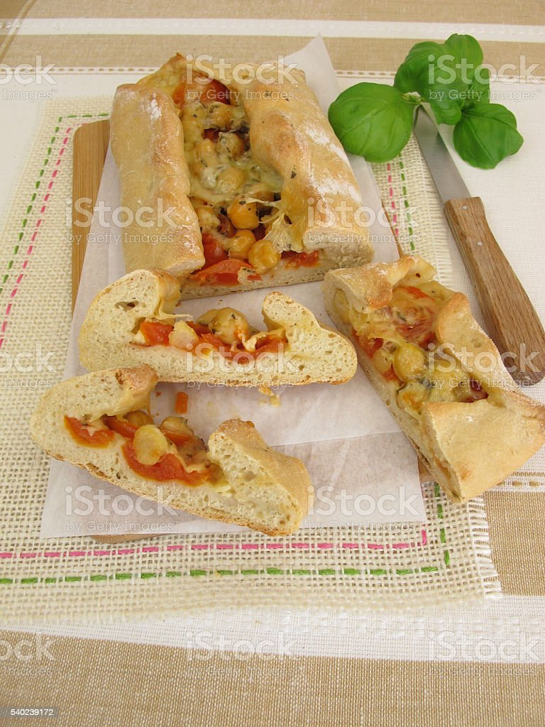Pizza bread filled with chickpeas, tomatoes and cheese stock photo