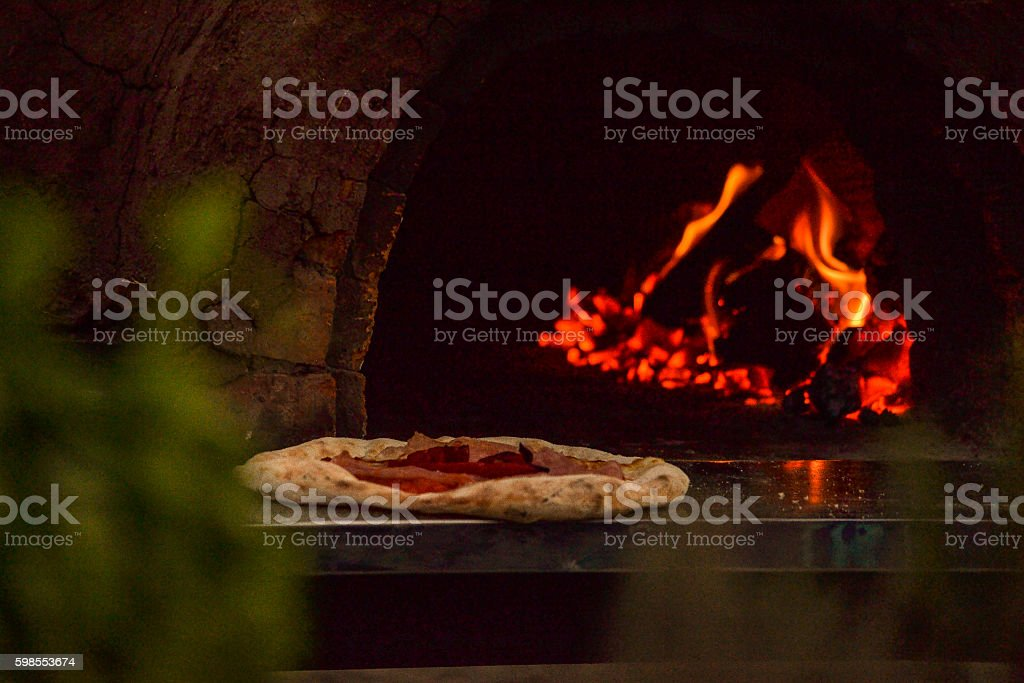 Pizza clay oven baked fire at back stock photo