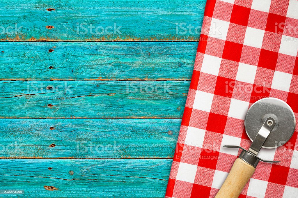 Pizza Cutter on Red White Checked Napkin Blue Rustic Wood stock photo