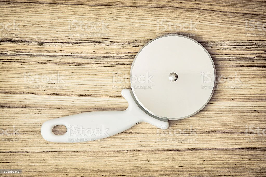 Pizza cutter on the wooden background, kitchen equipment stock photo