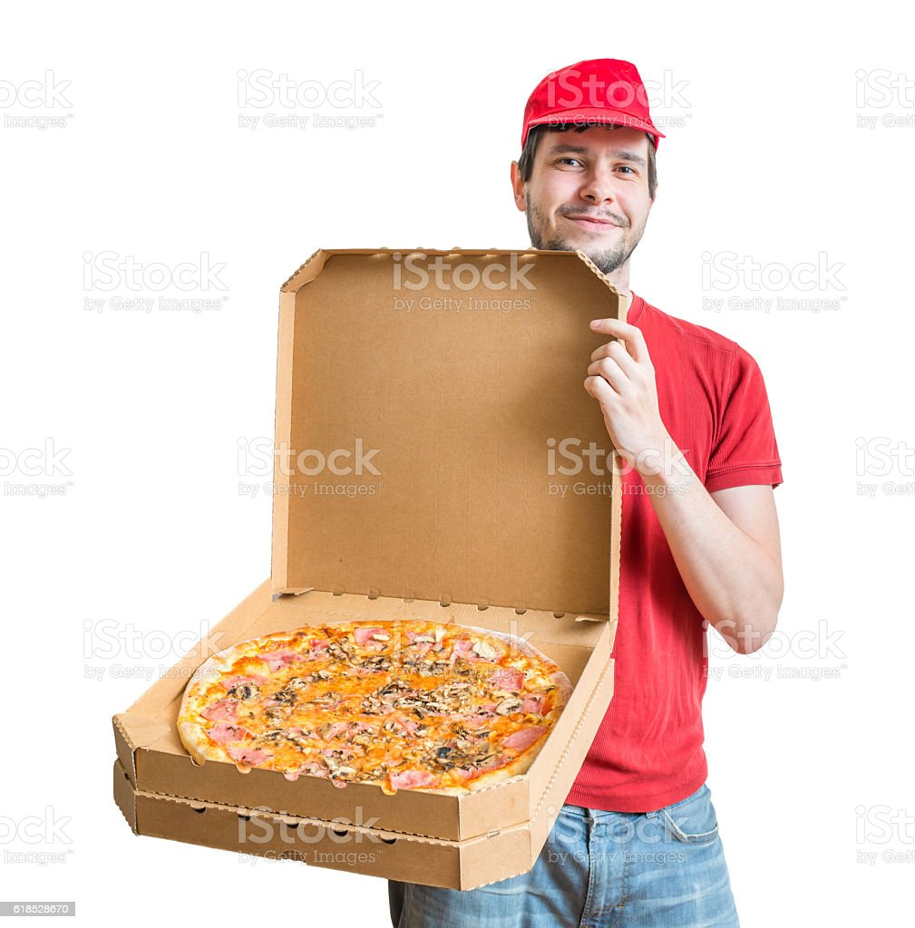 Pizza delivery concept. Young guy is showing tasty pizza. stock photo