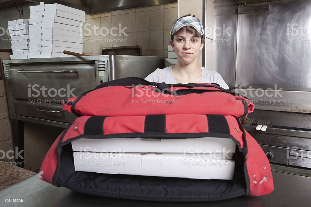 Pizza delivery girl preparing an order for delivery stock photo
