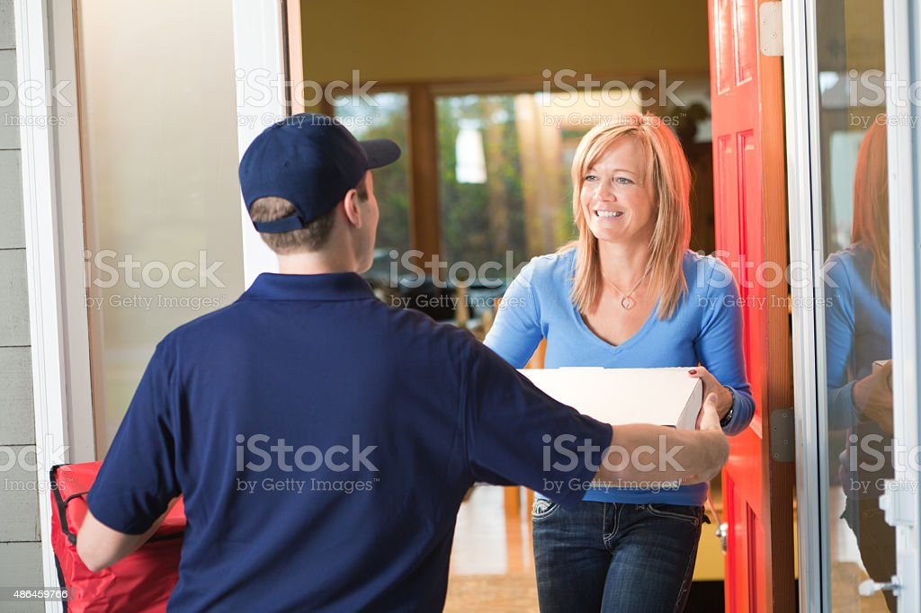 Pizza Delivery Man with Take-out Box at Customer's Home stock photo