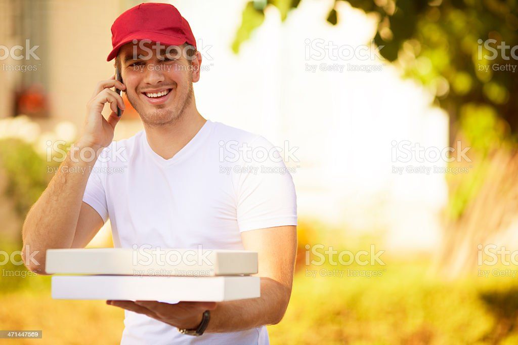 Portrait of an smiling young man with hat, working as pizza delivery...