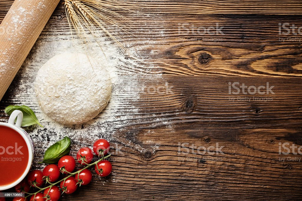 Pizza dough with ingredients on wood stock photo