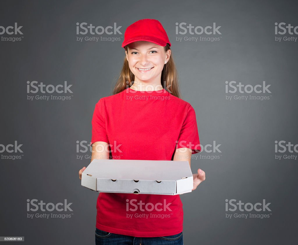 Pizza girl in red uniform delivering pizza isolated on grey. stock photo