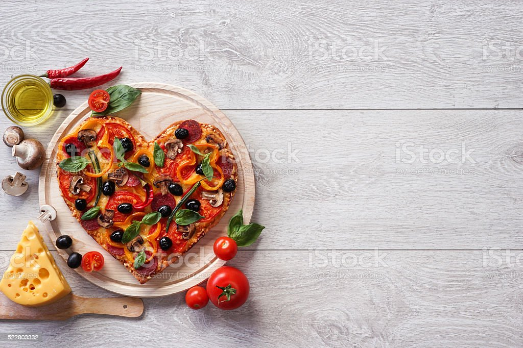 Pizza heart shape with ingredients and copy space stock photo
