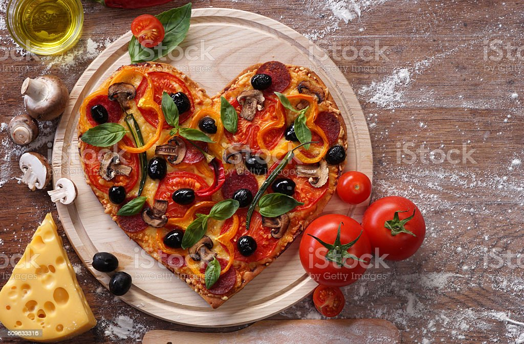 Pizza heart shape with ingredients on vintage boards. stock photo