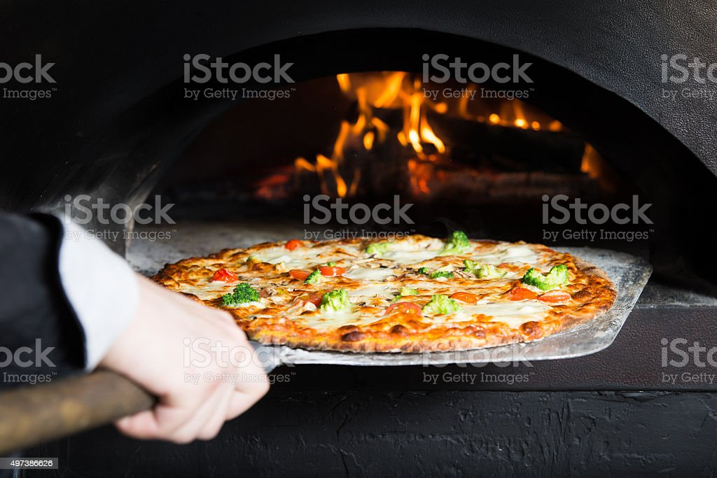 Pizza is moving out at peel from hot slove stock photo