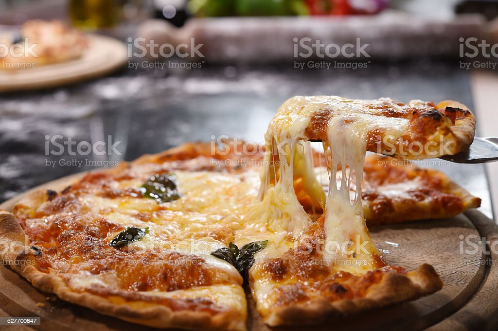 Pizza lifting slice on wooden board stock photo