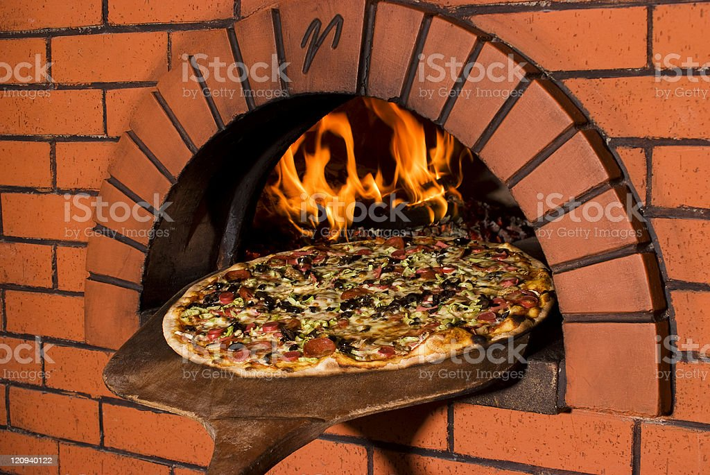 Pizza on a pizza plank and a light oven stock photo