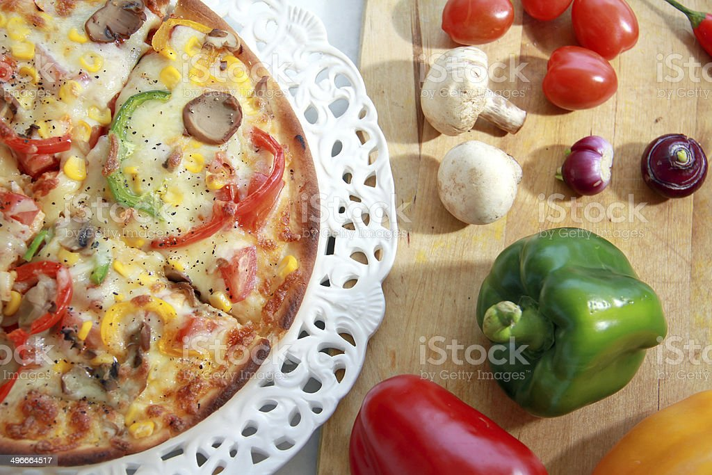 Pizza on plate & directly above & fresh vegetables beside the dish stock photo