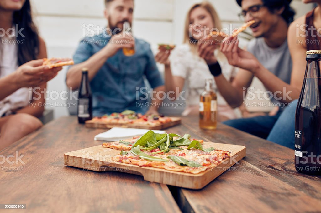 Pizza on table with friends enjoying party stock photo