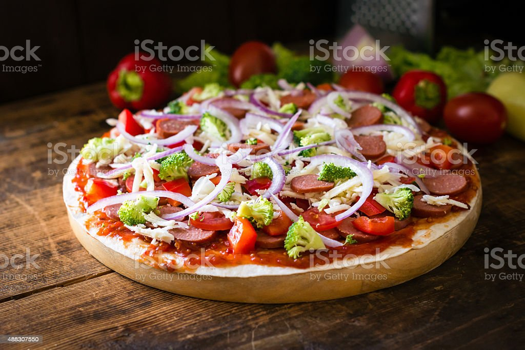 Pizza on wooden pizza board stock photo