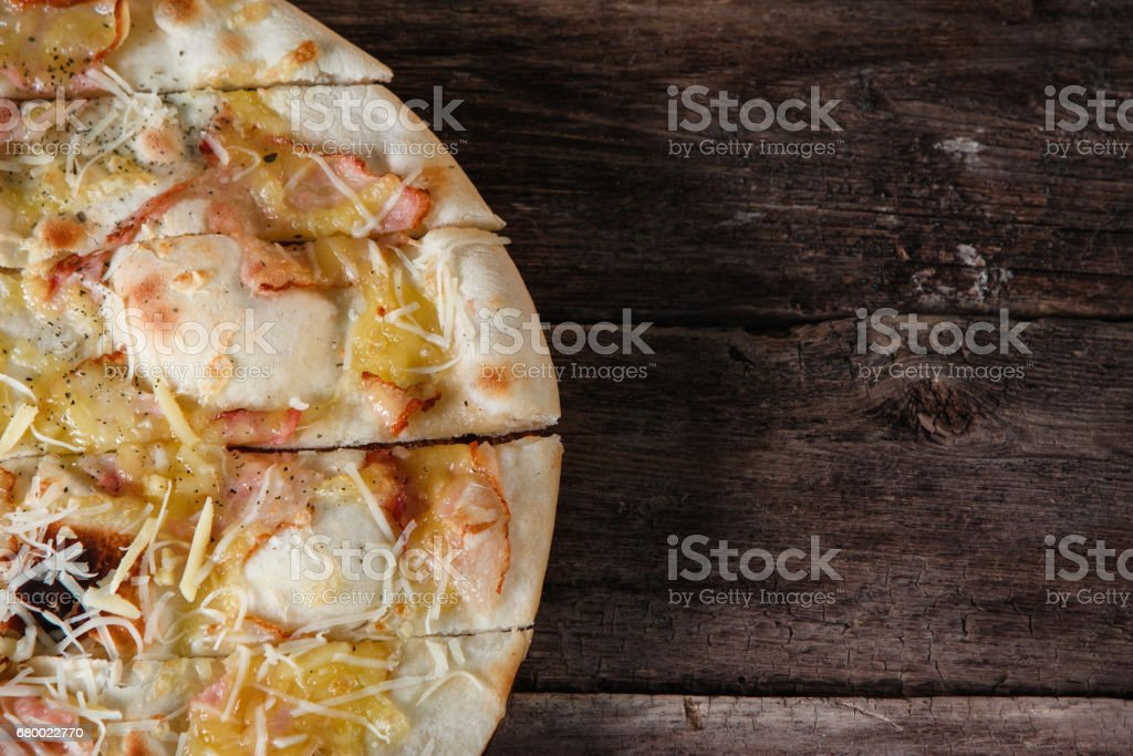 Pizza on wooden table. Junk food, unhealthy habits stock photo