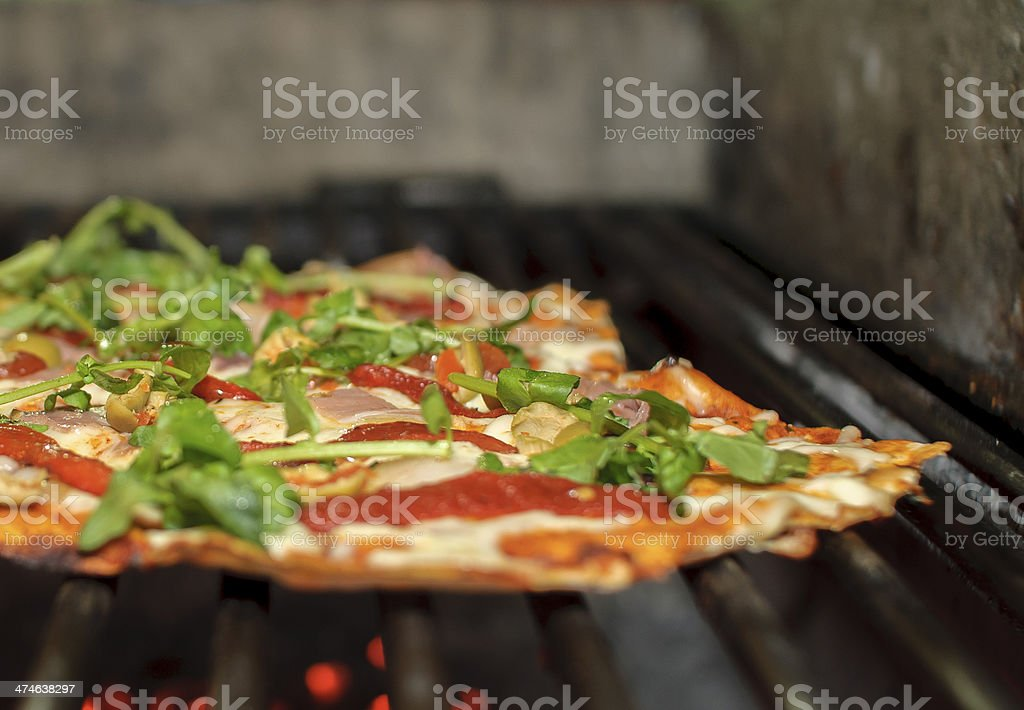 Pizza over grill stock photo