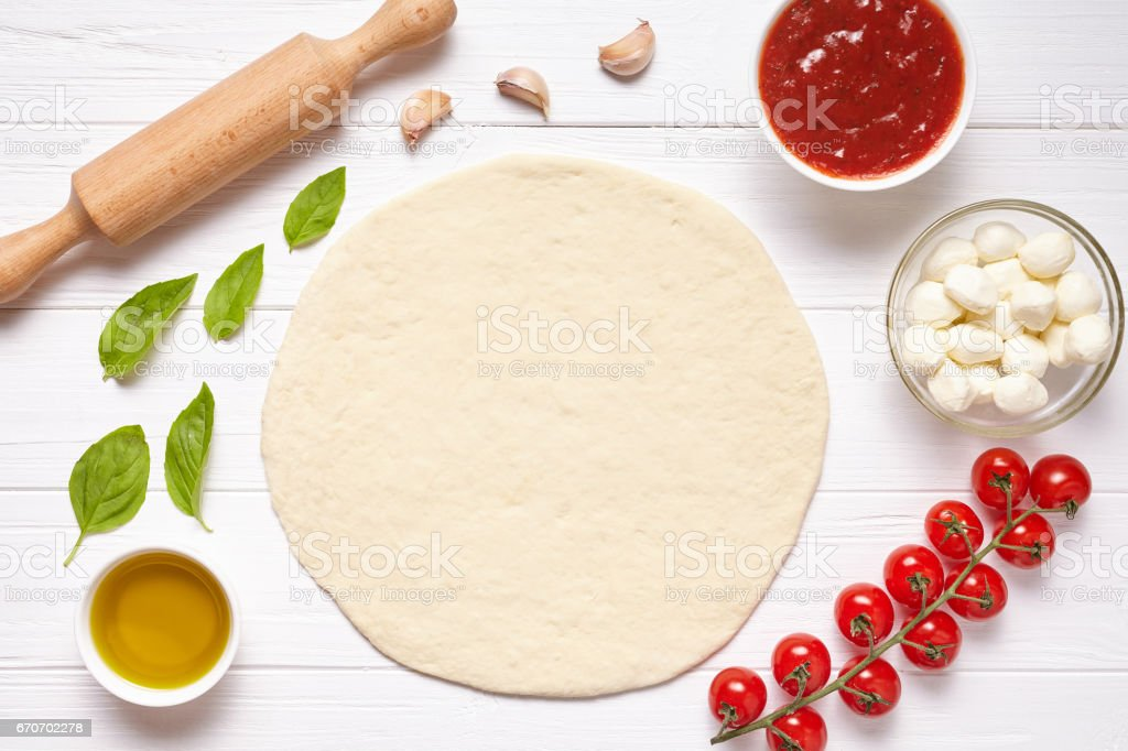 Pizza preparation. Baking ingredients on the kitchen table: rolled dough, mozzarella, tomatoes sauce, basil, olive oil, tomatoes, cheese, spices. stock photo