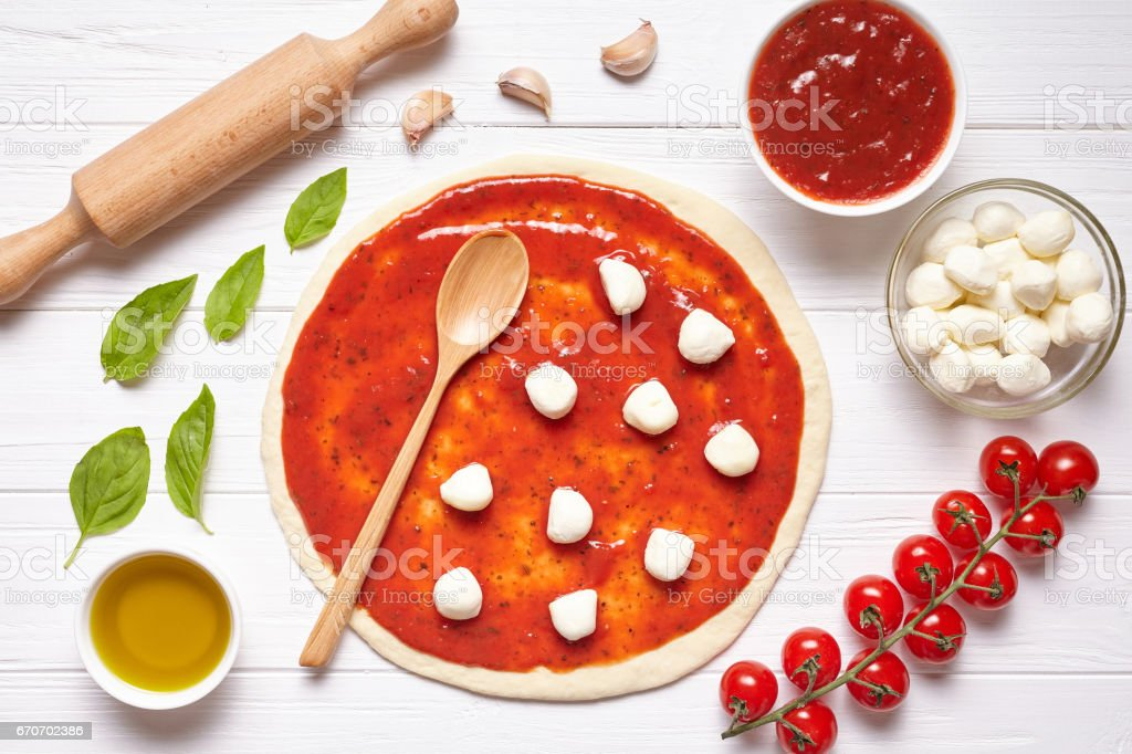 Pizza preparation. Ingredients on the kitchen table: rolled dough with tomatoes sauce, basil, olive oil, mozzarella cheese stock photo