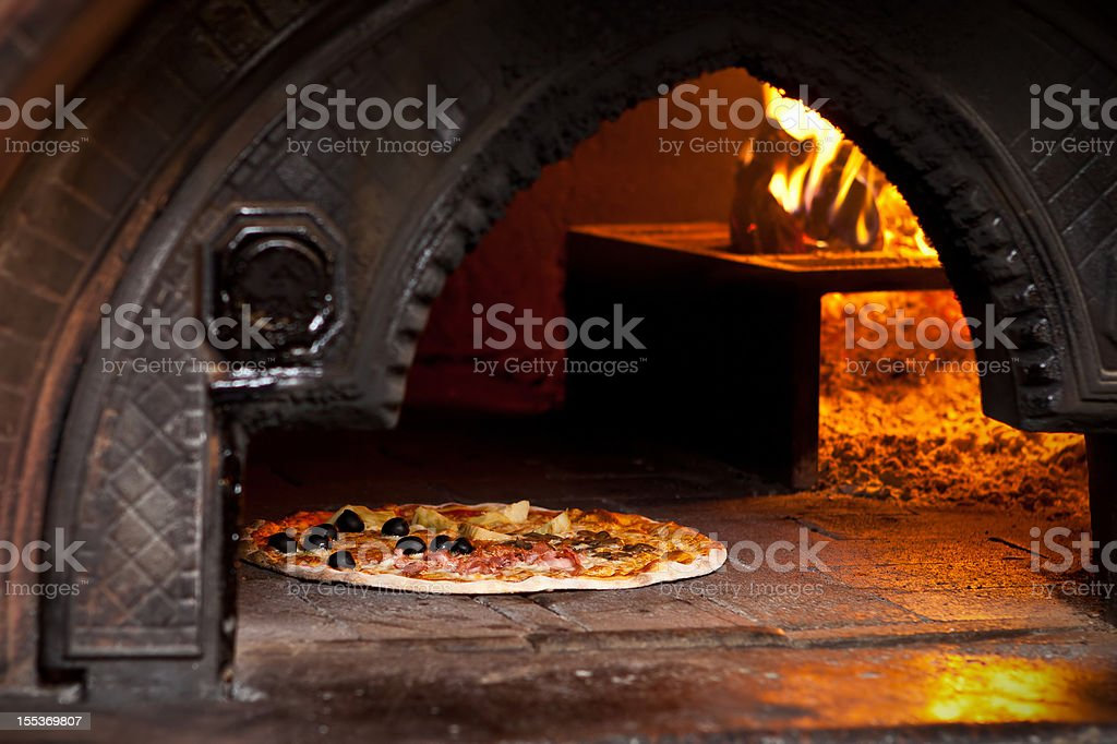 Pizza quattro stagioni (Four Seasons) in wood oven stock photo