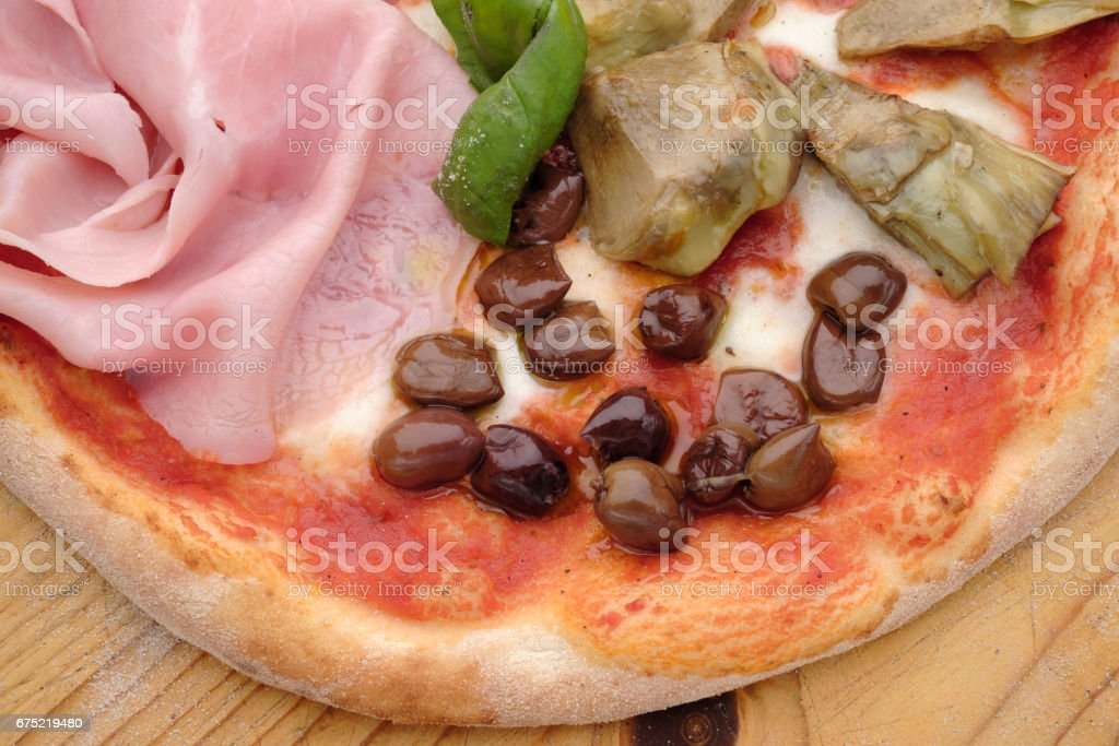 Pizza Quattro Stagioni, with ham and artichokes stock photo