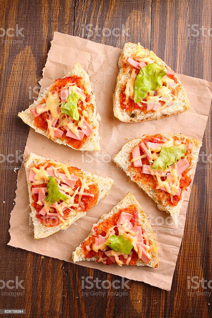 Pizza slices on parchment on wooden background stock photo