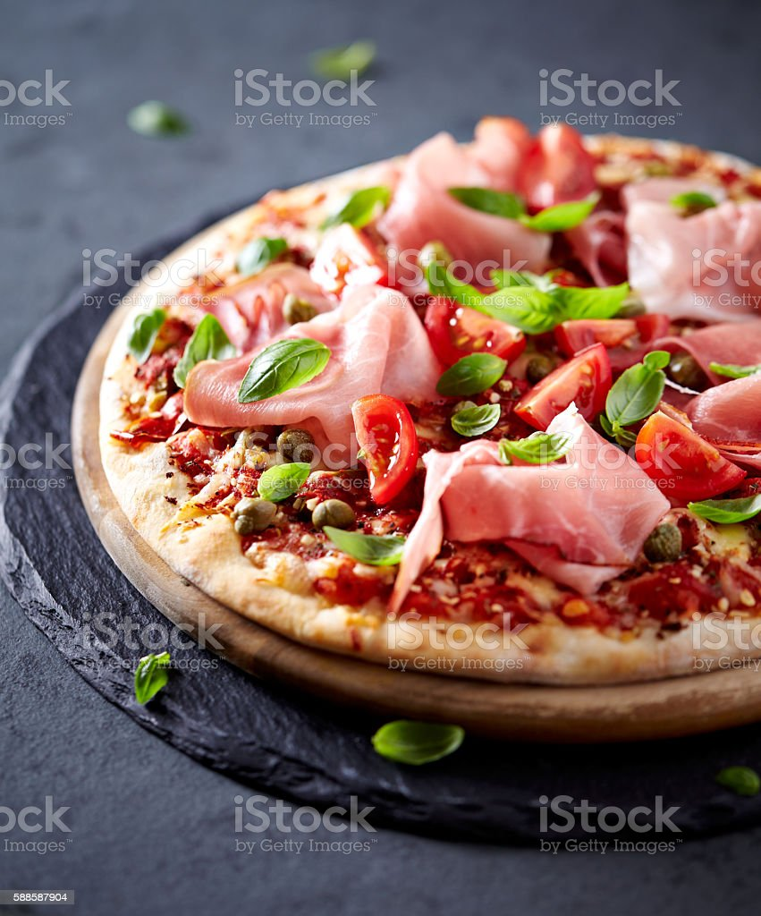 Pizza topped with Black Forest Ham, Cherry Tomatoes and Capers stock photo